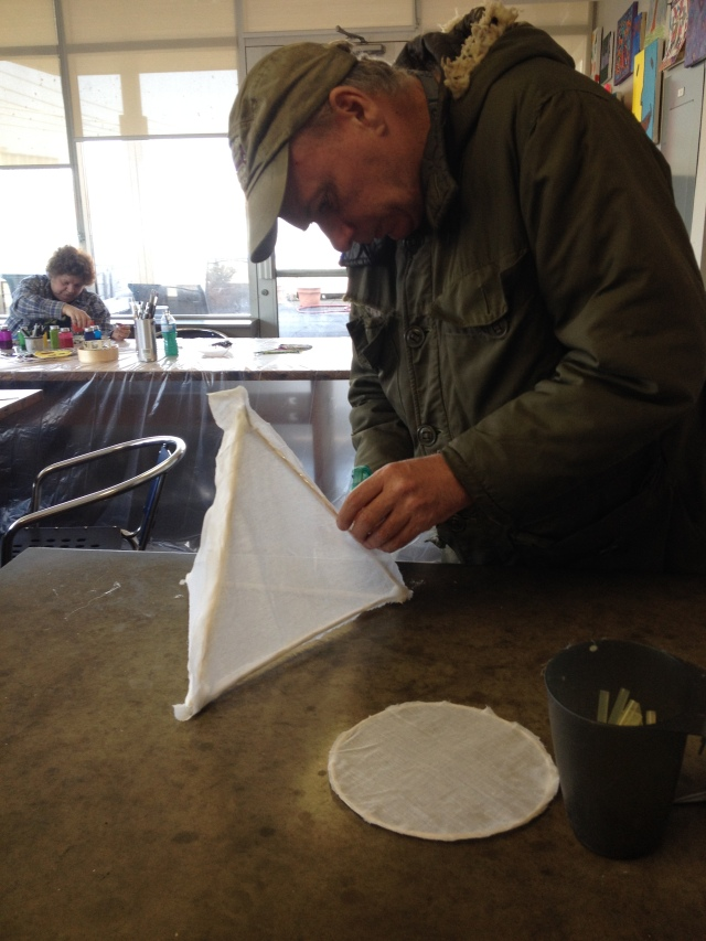 Lawrence attaches fabric to his pyramid frame
