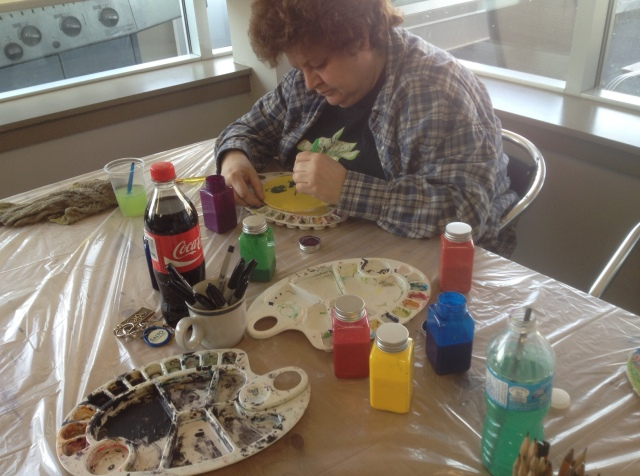 Donna paints on a fabric panel